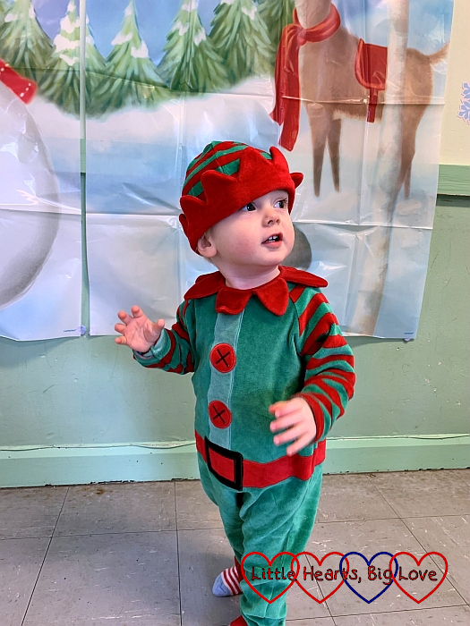 Thomas standing in front of a Christmassy backdrop, wearing an elf costume and hat