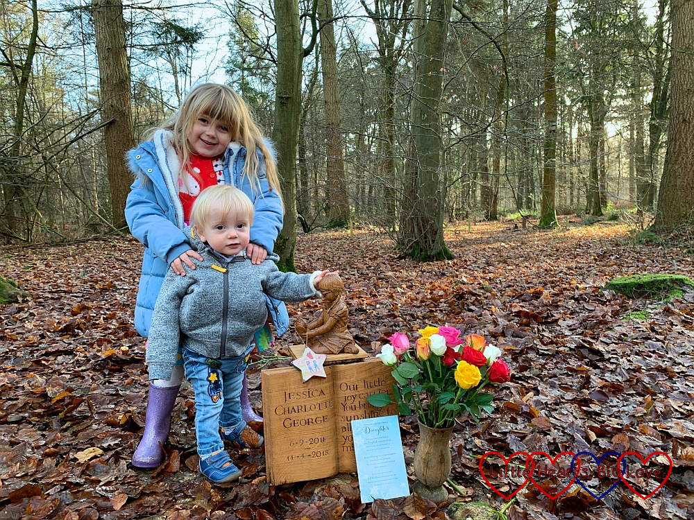 Sophie and Thomas standing next to Jessica's memorial at her forever bed with a Christmas bauble hanging from Jessica's Kerry doll, a daughter card propped against Jessica's memorial and a bouquet of colourful roses in a wooden vase