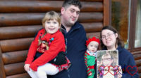 Hubby holding Sophie (wearing a reindeer Christmas jumper) and me holding Thomas (dressed as an elf) and a photo of Jessica outside Heligan Lodge at Coombe Mill