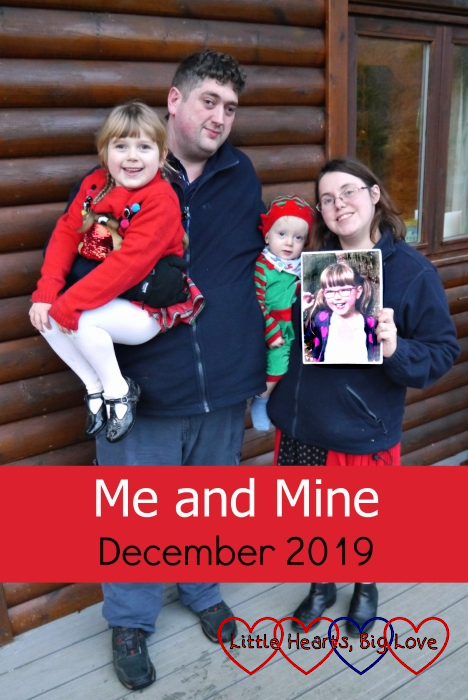 "Hubby holding Sophie (wearing a reindeer Christmas jumper) and me holding Thomas (dressed as an elf) and a photo of Jessica outside Heligan Lodge at Coombe Mill - ""Me and Mine - December 2019"""