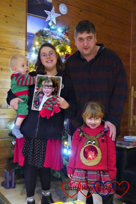 Hubby with Sophie (wearing a reindeer Christmas jumper) standing in front of him and me holding Thomas (dressed as an elf) and a photo of Jessica next to him, standing in front of a Christmas tree at Coombe Mill