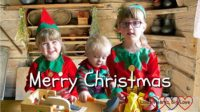 "Sophie, Thomas and Jessica dressed as Christmas elves at the table together with a log cabin background with the text ""Merry Christmas"" across the photo"