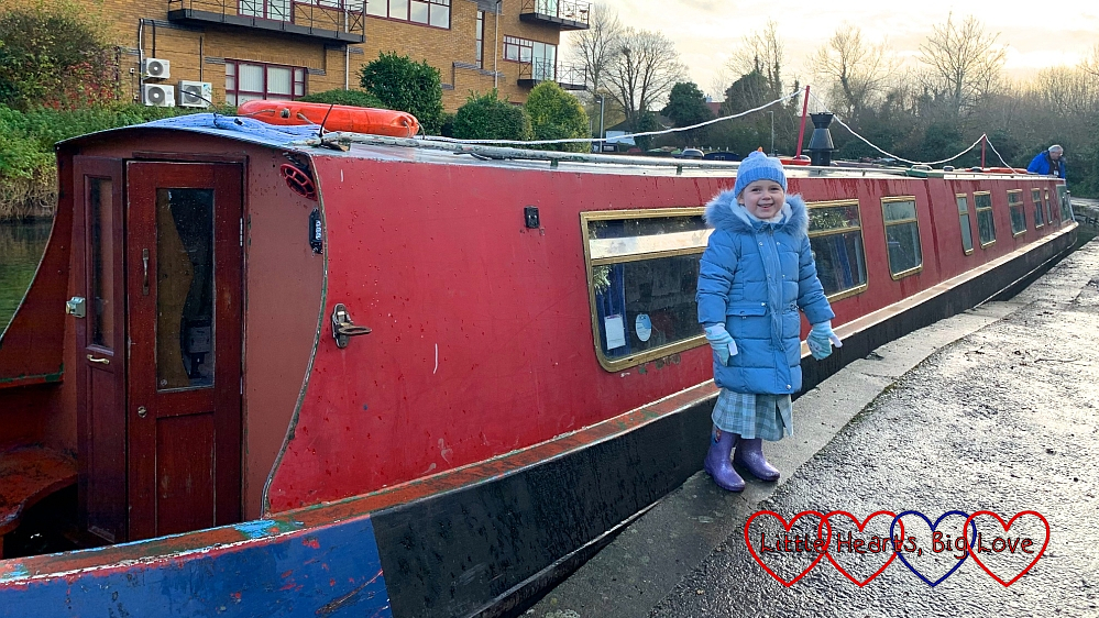 Sophie standing in front of a red narrowboat