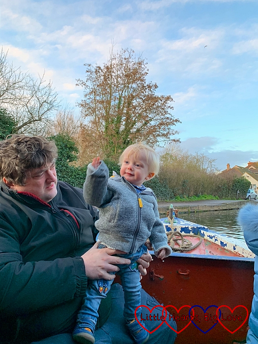 Thomas standing on Daddy's knees at the front of the narrowboat with the canal in the background