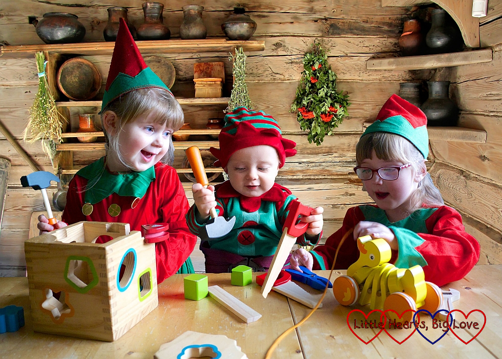 Sophie, Thomas and Jessica dressed as Christmas elves at the table together with a log cabin background