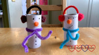 Two snowmen made from white paper covered toilet roll tubes with pipe cleaner and pompom scarves and earmuffs