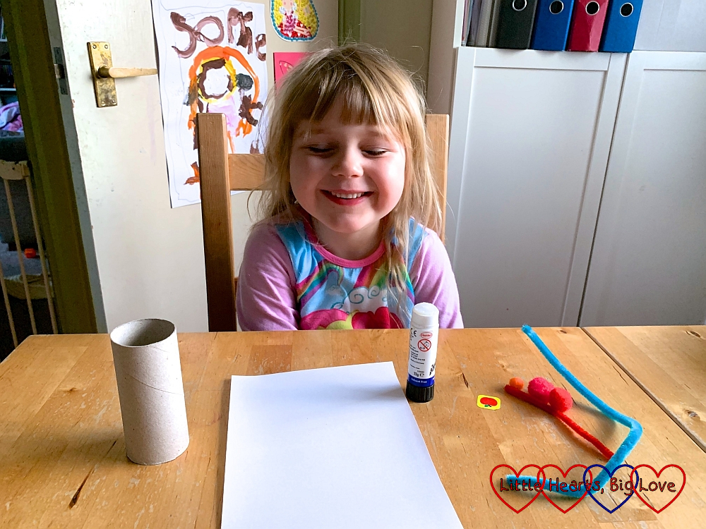 Sophie sitting at the table with a toilet roll tube, a sheet of white paper, a glue stick and some colourful pipe cleaners and pompoms