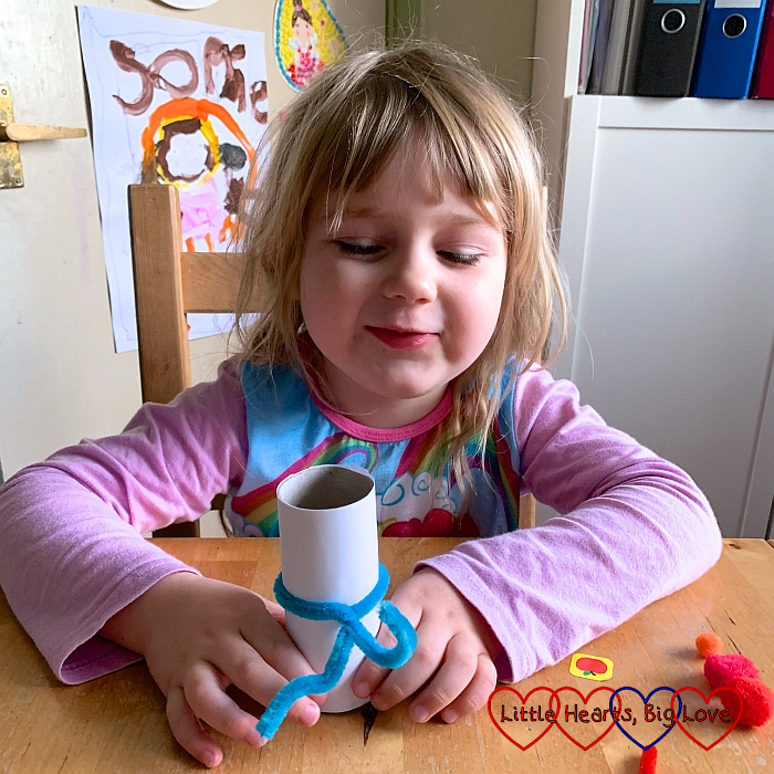 Sophie wrapping a blue pipe cleaner around the white-paper-covered toilet roll tube