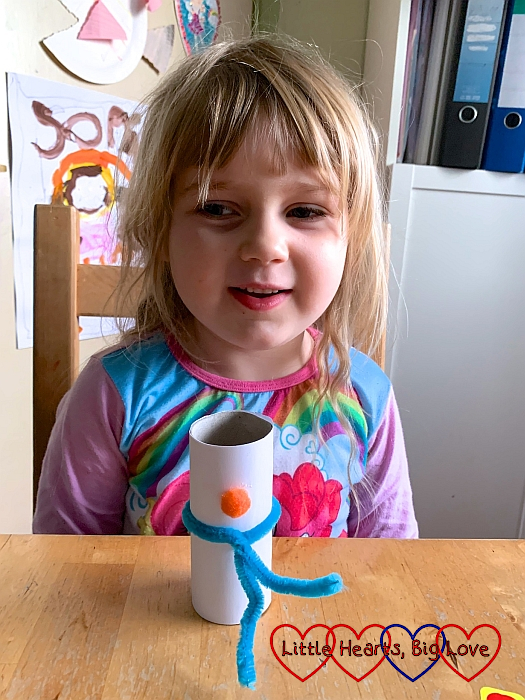 Sophie with the white paper covered toilet roll tube with a blue pipe cleaner wrapped around it and an orange pompom stuck to the top half
