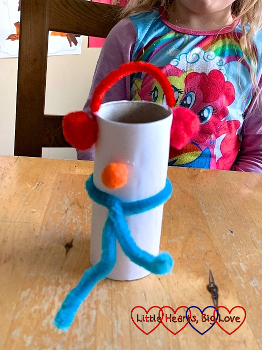 The white-paper-covered toilet roll tube with red pompom and pipe cleaner earmuffs, a blue pipe cleaner scarf and an orange pompom for the nose