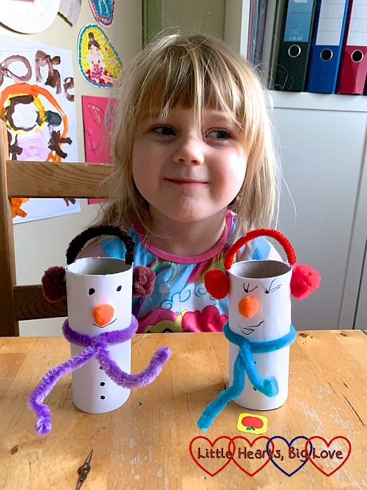 Sophie with the finished snowmen made from white paper covered toilet roll tubes with pipe cleaner and pompom scarves and earmuffs