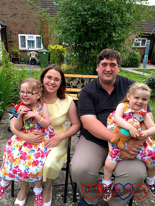 Me with Jessica on my lap and hubby with Sophie on his lap sitting on a bench in my mum's garden in July 2016