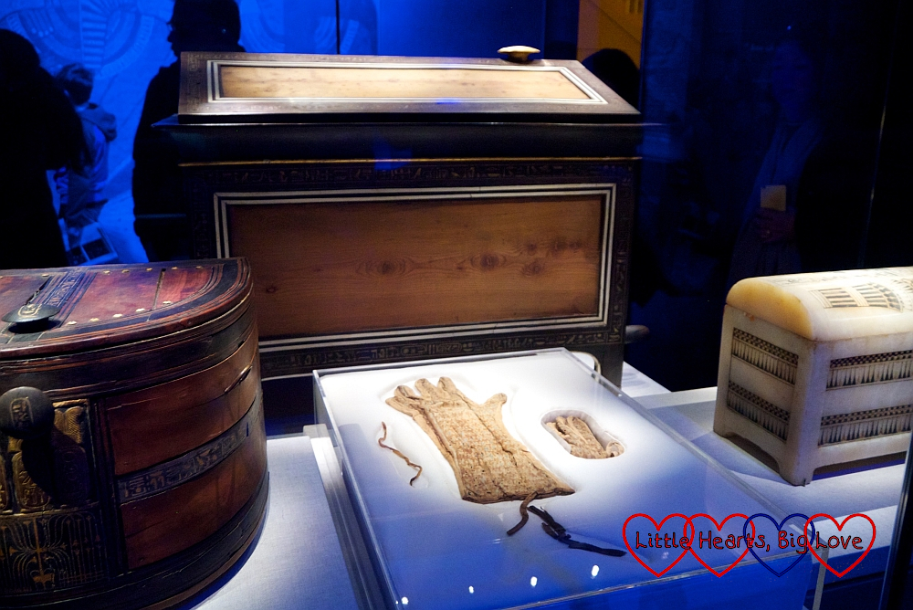 A pair of woven tapestry linen gloves in front of a wooden travelling chest at the Tutankhamun exhibition