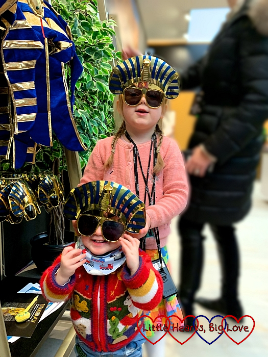 Sophie and Thomas in the gift shop at the Tutankhamun exhibition wearing sunglasses with the a gold and blue mask at the top