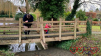 Daddy and Sophie playing Poohsticks on a wooden bridge over a stream