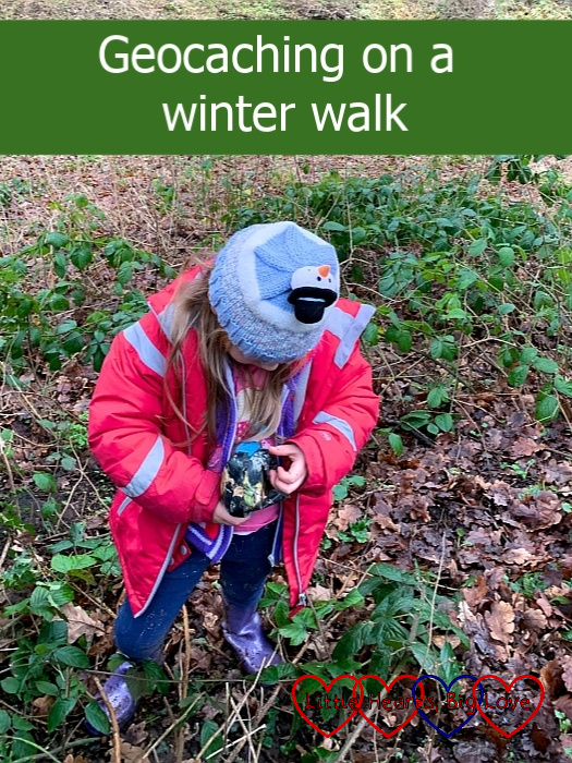 """Sophie holding a geocache covered in camouflage tape - """"Geocaching on a winter walk"""""""