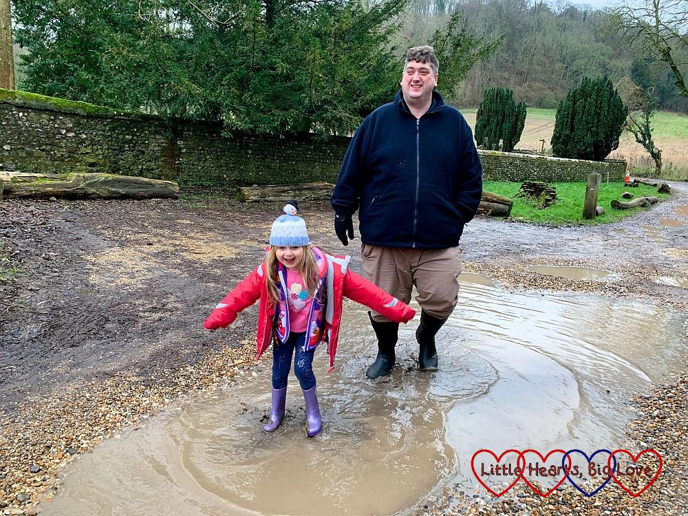 Sophie and Daddy splashing in a big puddle