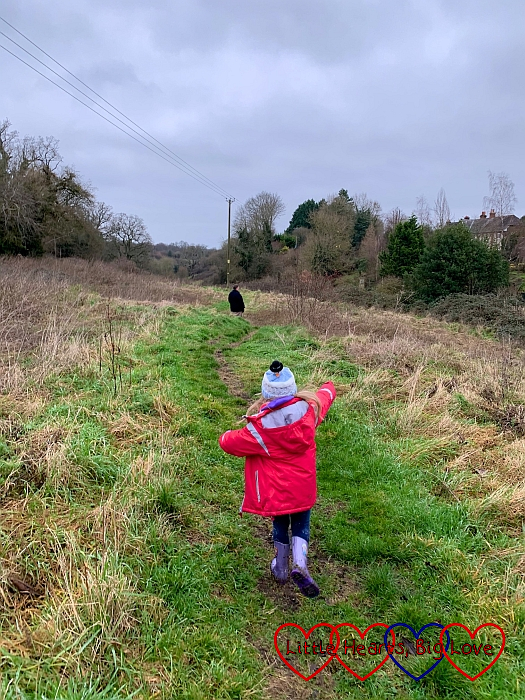 Sophie walking along a grassy footpath with Daddy up ahead of her