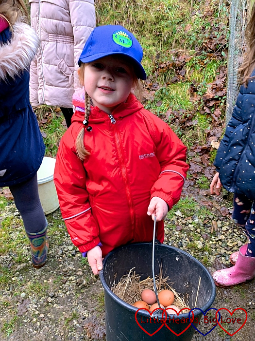 Sophie holding a bucket containing the eggs collected from the chickens