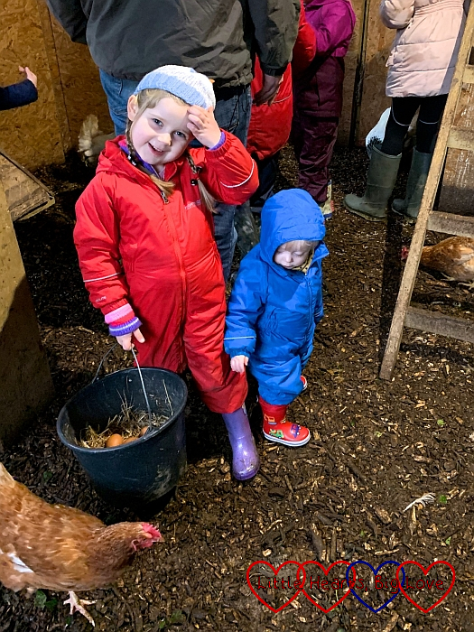 Sophie in the chicken coop holding a bucket of eggs with Thomas standing next to her looking at a chicken