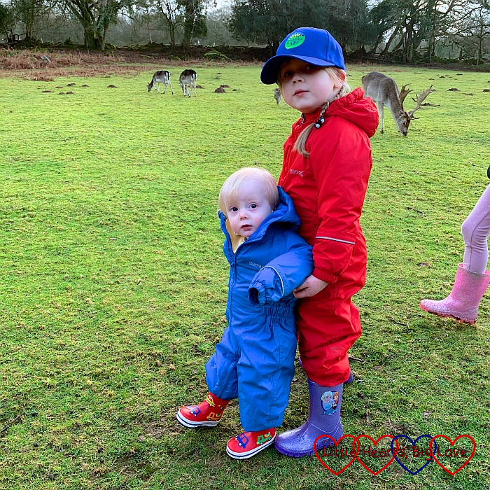 Thomas and Sophie wearing puddlesuits and wellies in the deer field at Coombe Mill with the deer in the background