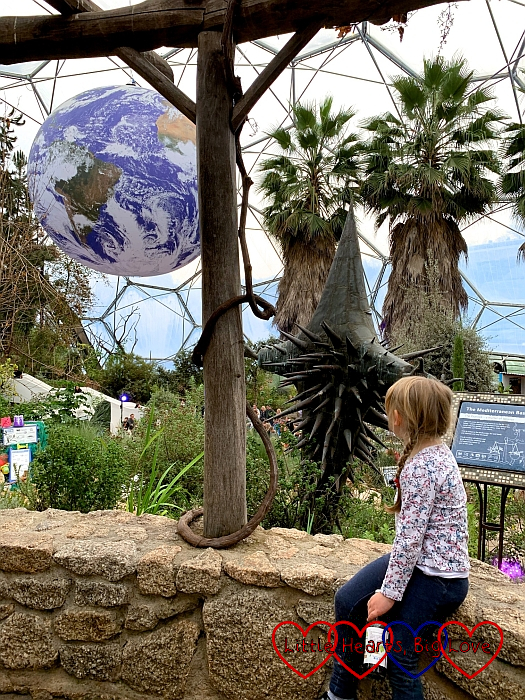 Sophie in the Mediterranean biome at the Eden Project, looking at a large globe suspended from the roof