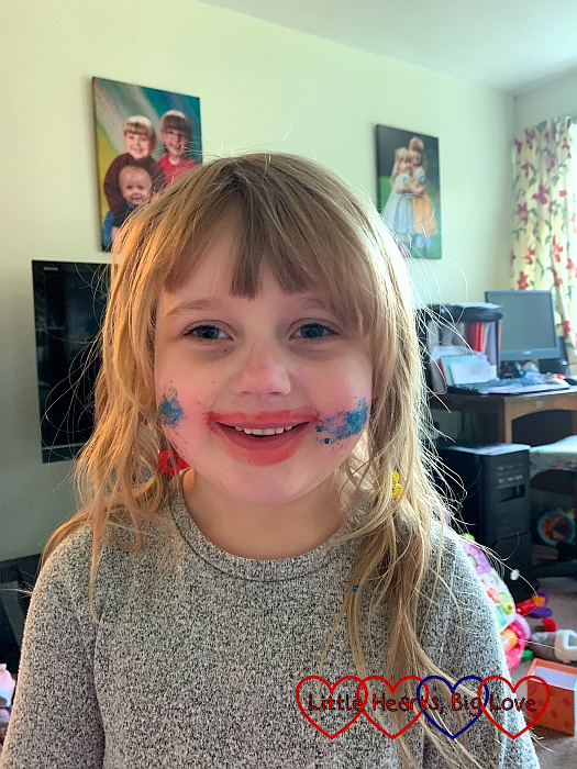 Sophie looking like a clown with pink lipstick smeared around her mouth and blue eyeshadow on her cheeks