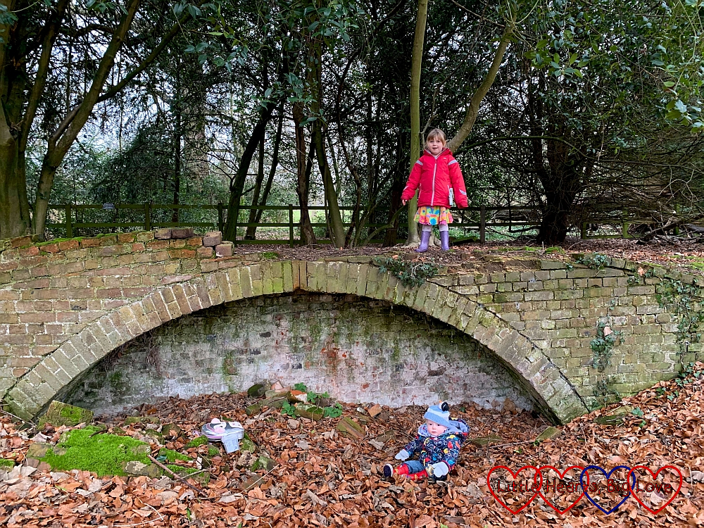 Sophie standing on top of a brick arch with Thomas sitting in leaves underneath