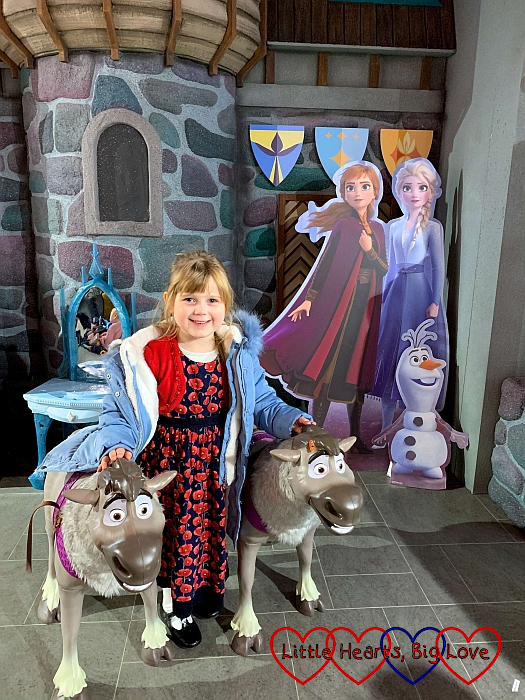 Sophie standing by the Frozen 2 display in Hamleys between two moving Sven reindeers