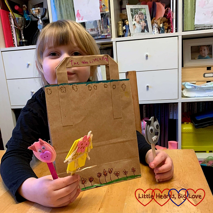 Sophie with her story bag and three craft stick puppets of a pig, the Big Bad Wolf and the straw house