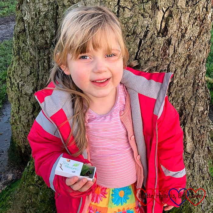 Sophie standing in front of a tree and holding a matchbox with 'Tiny Treasures' written on it