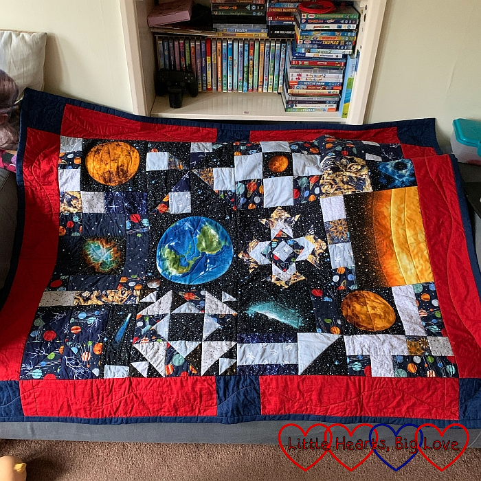 Thomas's space themed quilt with planets and stars on it