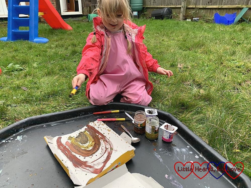 Sophie painting using a mixture of mud and paint on pieces of cardboard on the tuff tray in the garden