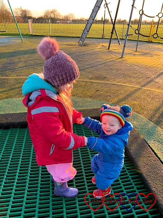 Sophie holding Thomas's hands and gently bouncing on the trampoline at the park
