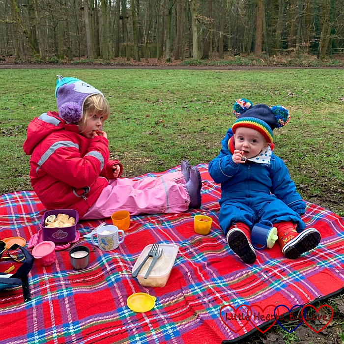 Sophie and Thomas wearing winter coats and hats, sitting on a picnic blanket, having a picnic in the park