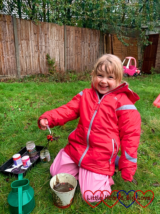 A very smiley Sophie mixing a mud potion in the garden