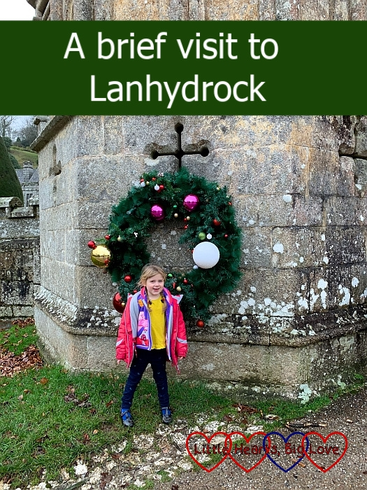 "Sophie standing in front of one of the large Christmas wreaths on the gatehouse at Lanhydrock - ""A brief visit to Lanhydrock"""