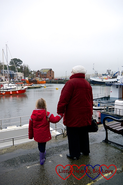 Sophie holding Grandma's hand looking at the boats at Padstow