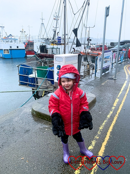 Sophie in front of a boat in Padstow harbour, wearing Grandad's big gloves