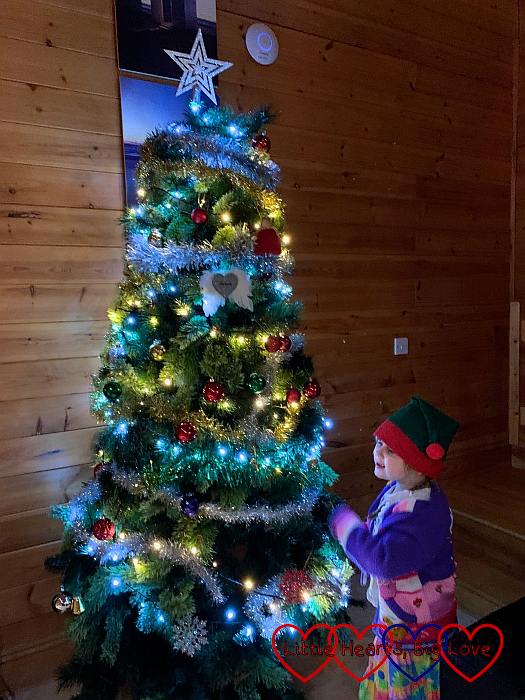Sophie wearing an elf hat and decorating the Christmas tree in Heligan Lodge