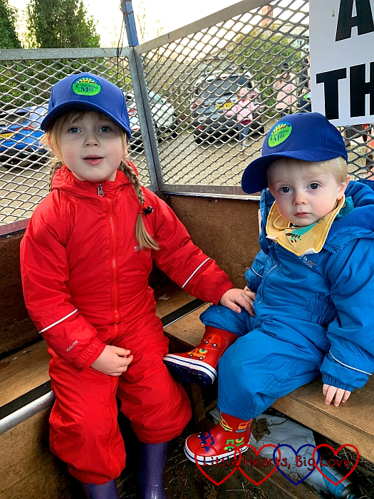 Sophie and Thomas wearing puddlesuits and Coombe Mill hats sitting in the trailer ready for the feed run