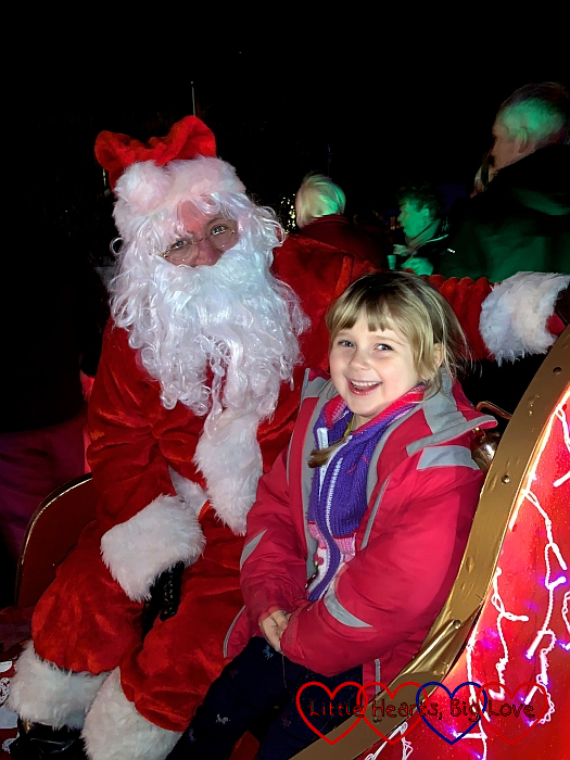 Sophie sitting with Father Christmas in his sleigh at St Tudy