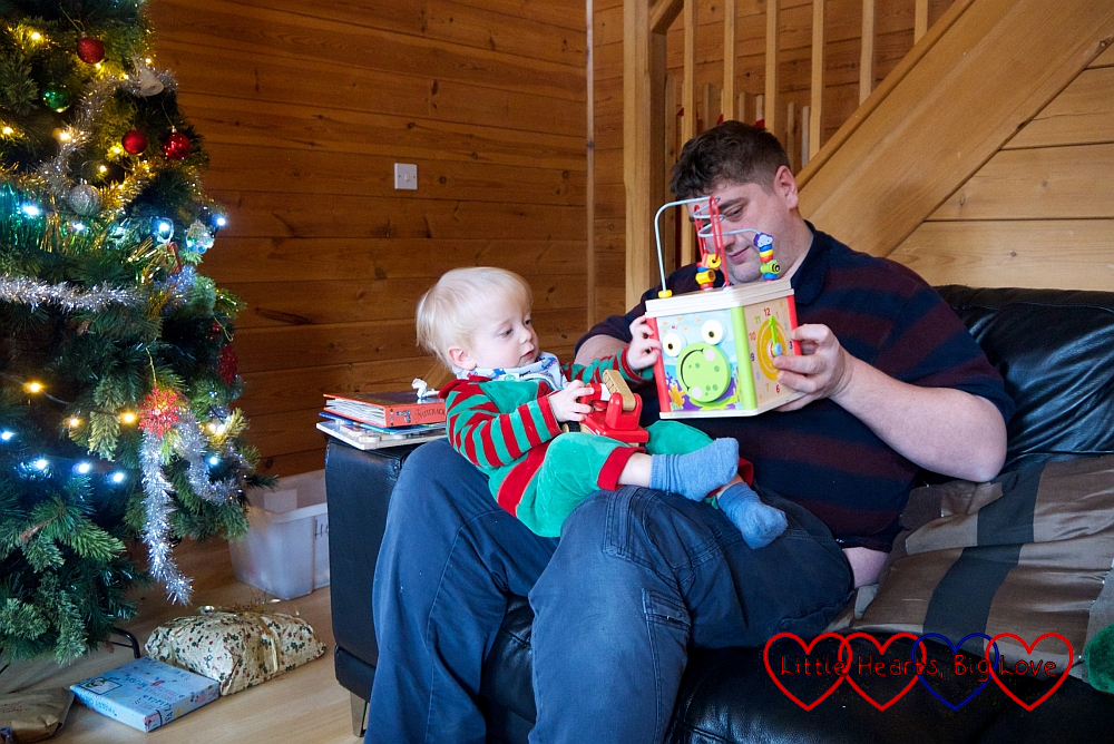 Thomas wearing an elf costume, sitting on Daddy's lap and opening Christmas presents in Heligan Lodge