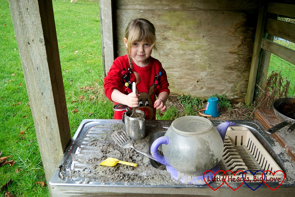 Sophie mixing a muddy mixture in a teapot in the mud kitchen