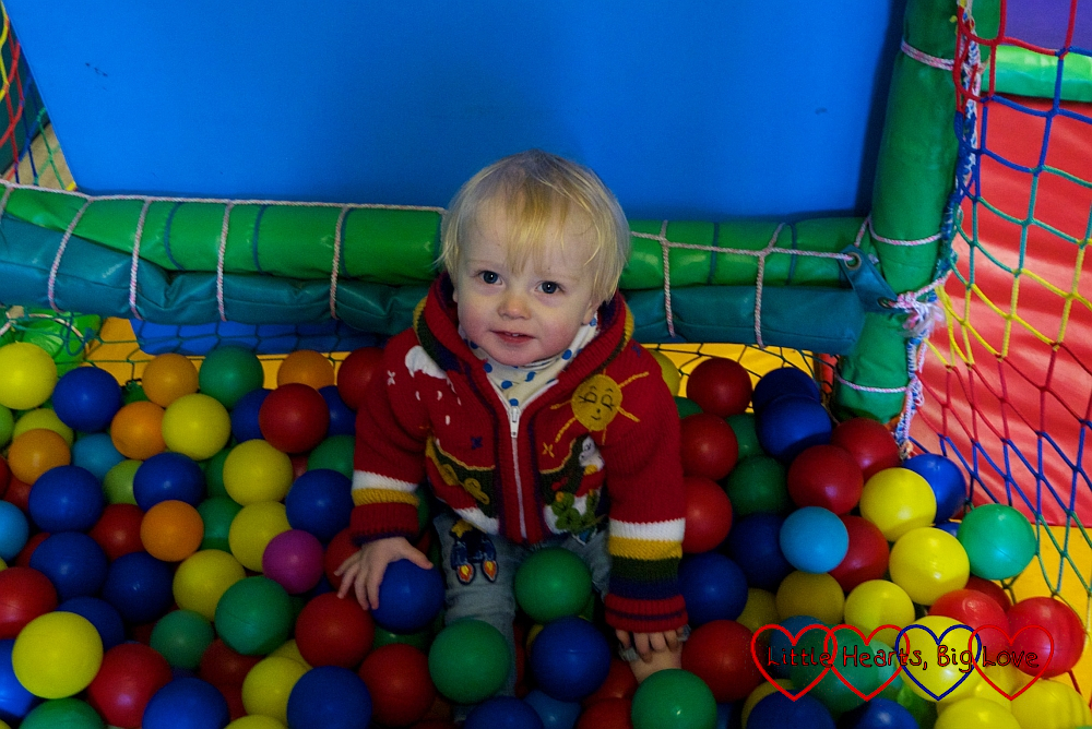 Thomas sitting in the ball pit in the play barn at Coombe Mill