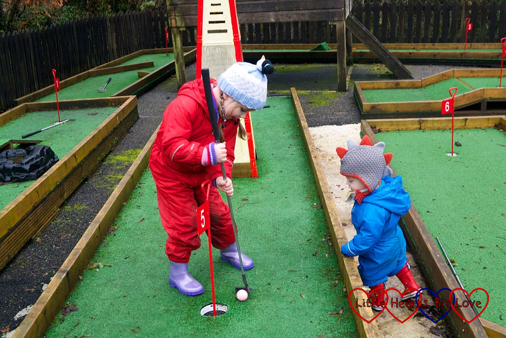 Thomas watching Sophie playing crazy golf at Coombe Mill