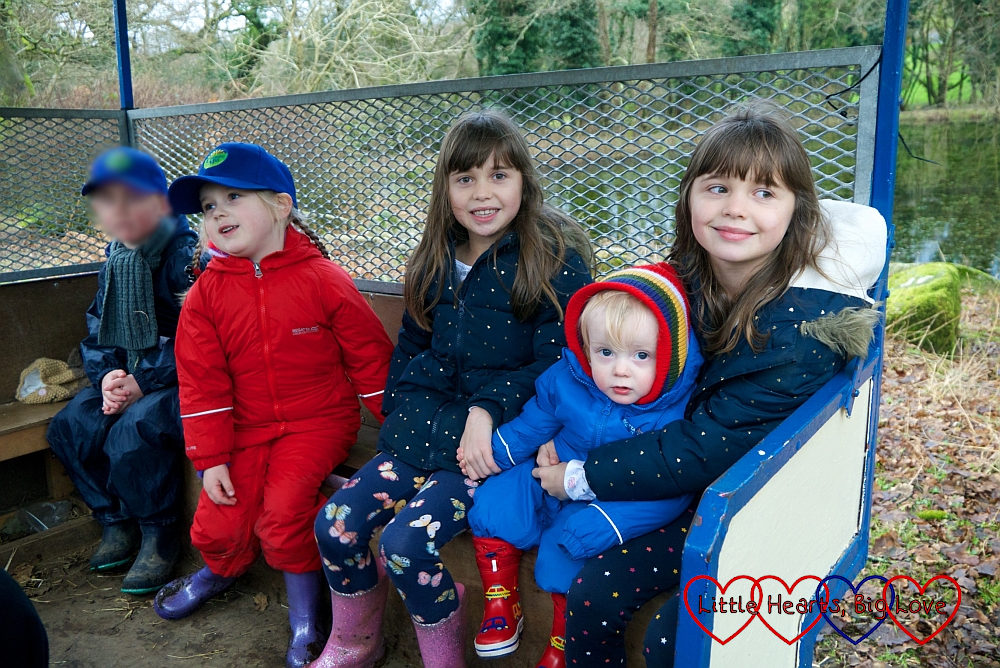 Sophie and Thomas sitting with twin girls in the trailer at Coombe Mill