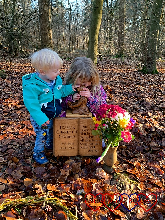 Thomas and Sophie holding and looking at the carving of Jessica on her memorial at her forever bed
