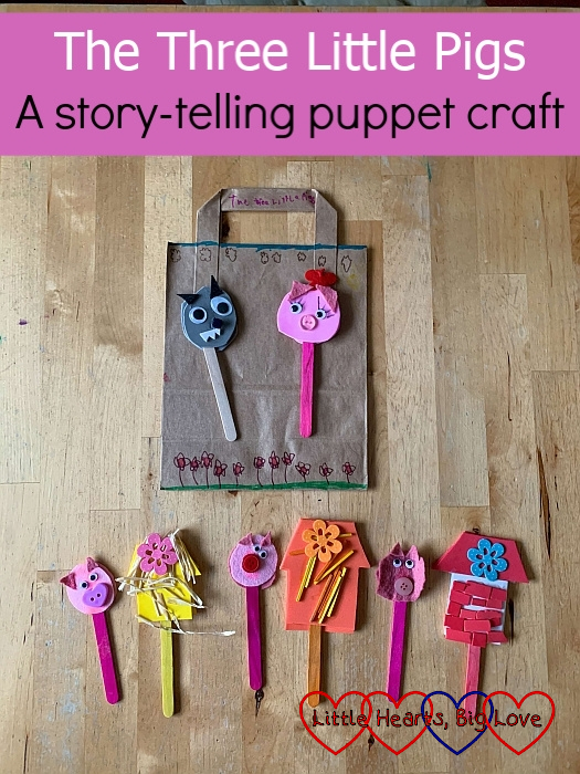 """The three houses made from felt/foam and a craft stick; the Three Little Pigs puppets, a Big Bad Wold puppet and Mummy Pig against the background of a brown paper bag decorated to be a background scene - """"The Three Little Pigs - A story-telling puppet craft"""""""