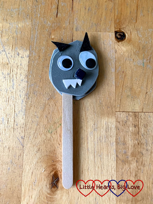The Big Bad Wolf puppet made from grey foam, a craft stick, googly eyes, white foam teeth and a black button for his nose
